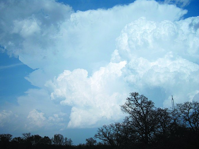 cumulonimbus tower in the foreground with a developing anvil in the background